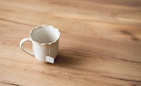 Closeup of a white ceramic cup with a bag of tea or herbal tea on wooden table. Archivio Fotografico