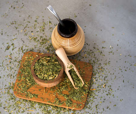 Traditional South American Yerba Mate tea in matero cup with bombilla metal straw servin photographed in modern kitchen