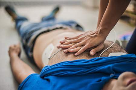 Cardiac Arrest: man given a cpr by a lady Stock Photo