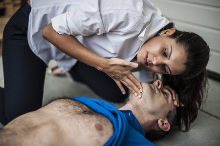 the unconscious: rescuer checking vital signs unconscious man Stock Photo