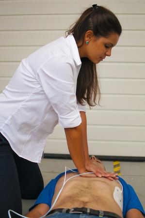ragazza esegue CPR al ragazzo privo di sensi Archivio Fotografico