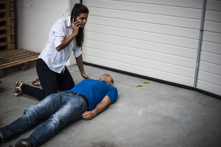 girl calls to emergency medical services to unconscious man Stok Fotoğraf