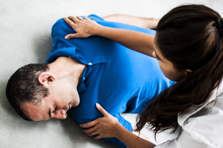 girl attends unconscious man after cardiac arrest Stock Photo - 64662046