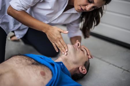 signos vitales: chica comprueba los signos vitales de un hombre inconsciente Foto de archivo