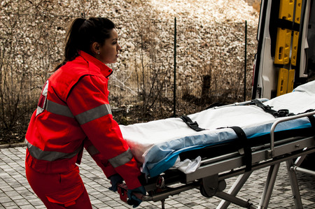 Voluntary girl of emergency services with stretcher