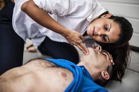 signos vitales: chica revisar los signos vitales de un hombre inconsciente