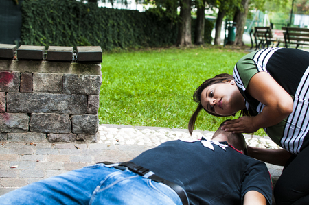 girl checking vital signs of unconscious boy after illness