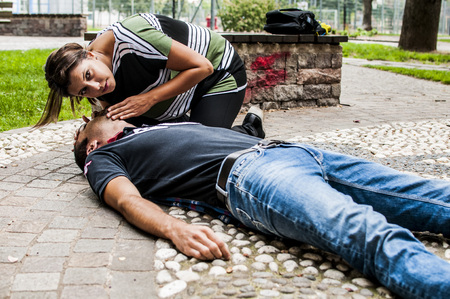 girl checking vital signs to unconscious boy after illness Stock Photo