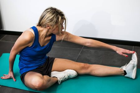 elongacion: chica haciendo ejercicios de fitness, estiramientos, levantamiento de pesas y abdominales Foto de archivo