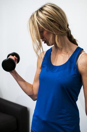alargamiento: chica haciendo ejercicios de fitness, estiramientos, levantamiento de pesas y abdominales Foto de archivo