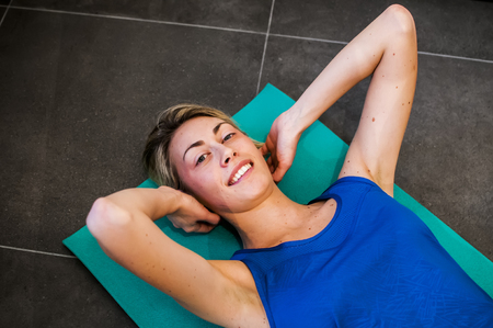 girl making fitness exercises, stretching, weight lifting and abdominals