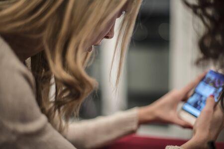 due ragazze parlando a casa a bere il tè caldo e una con uno smartphone