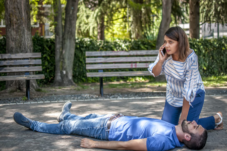 Girl calling emergency service for an unconscious guy