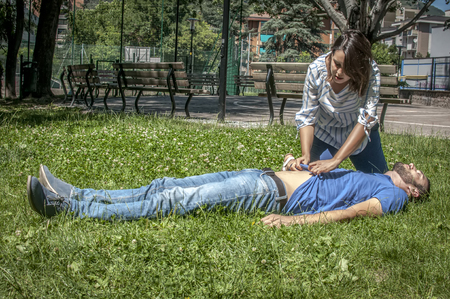 respiration: Girl making cardiopulmonary resuscitation to an unconscious guy after heart attack