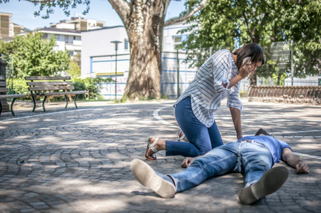 Girl calling emergency service to help a guy with cpr
