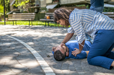 Girl trying to find help for an unconscious guy Stock Photo