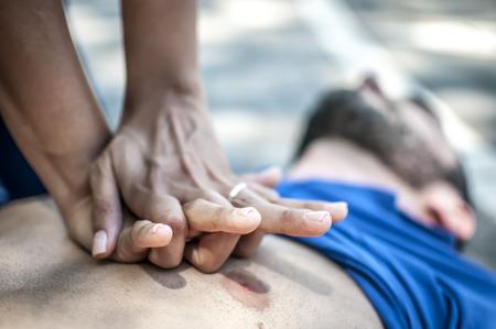 Meisje dat cardiopulmonale reanimatie maakt aan een onbewuste kerel na hartaanval Stockfoto