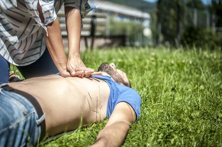 Ragazza che fa rianimazione cardiopolmonare a un ragazzo inconscio dopo attacco di cuore Archivio Fotografico - 81426897
