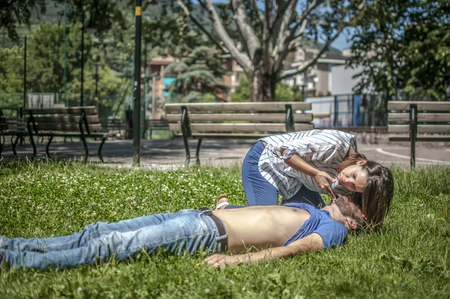 Girl checking the breathing of an unconscious guy after heart attack Stock Photo