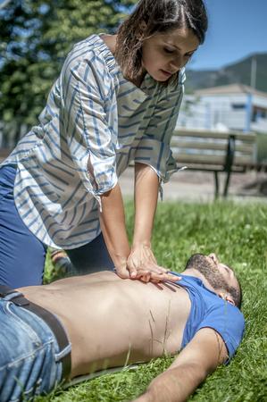 Ragazza che fa rianimazione cardiopolmonare a un ragazzo inconscio dopo attacco di cuore Archivio Fotografico - 81541378