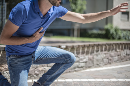 Guy searching help during a heart attack Stock Photo