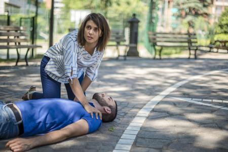 La ragazza assiste un ragazzo inconscio dopo l'incidente Archivio Fotografico - 82152715