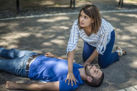 Meisje helpt na het ongeluk een bewusteloze man Stockfoto