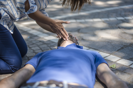 Girl checking vital parameters of an unconscious guy after heart attack Zdjęcie Seryjne