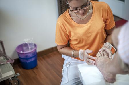podiatry doctor curing an elderly patient foot Zdjęcie Seryjne