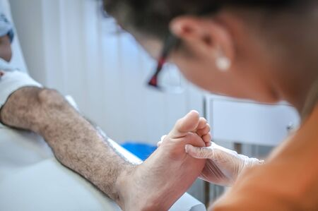 dedo meÑique: podiatry doctor curing a young patient feet