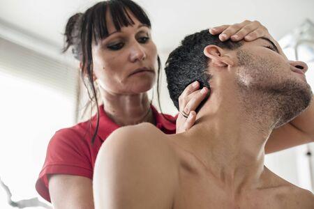 il fisioterapista massaggia il giovane paziente per curare un dolore cervicale Archivio Fotografico
