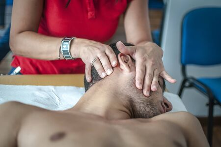 physiotherapist massages young patient to cure a cervical pain Archivio Fotografico
