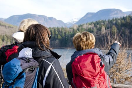 Three women observe the panorama of the lake in the mountains Stok Fotoğraf