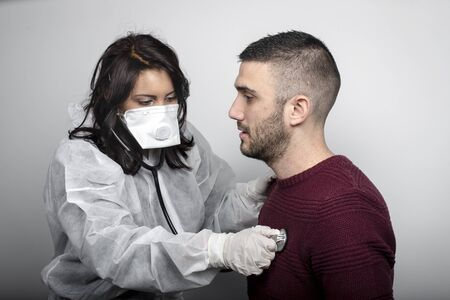 medical doctor with protection mask, glasses and suit assisting a patient
