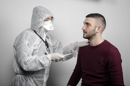 medical doctor with protection mask, glasses and suit measuring the temperature of a patient