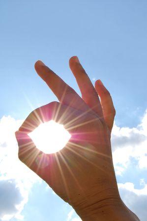 A OK sign through sun rays Stock Photo