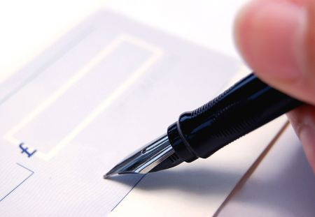 overdraft: Signing a blank cheque Stock Photo