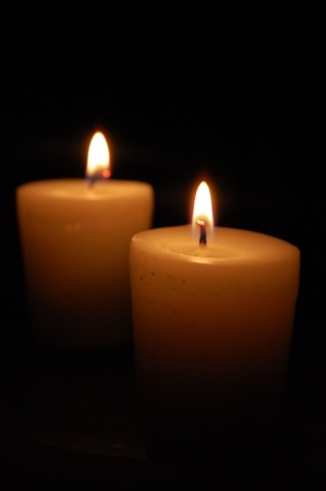 couple lit: Two lit candles glowing in the dark Stock Photo