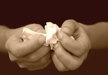 confide: Closeup of hands holding a tissue   Stock Photo