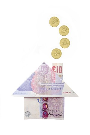 Pound coins emerging from a  house chimney made from pound banknotes  photo