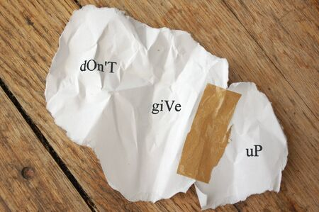 don't: Crumpled piece of torn paper stuck together with tape with the message dont give up
