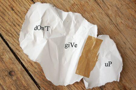 Verfrommeld stukje gescheurd papier geplakt samen met tape met de bericht dont geven