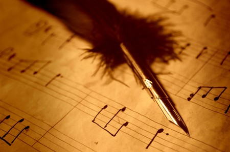 Quill pen on an old handwritten music sheet photo