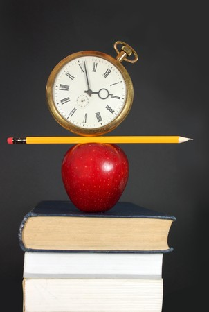 Clock and pencil balancing on top of a pile of books with an apple photo