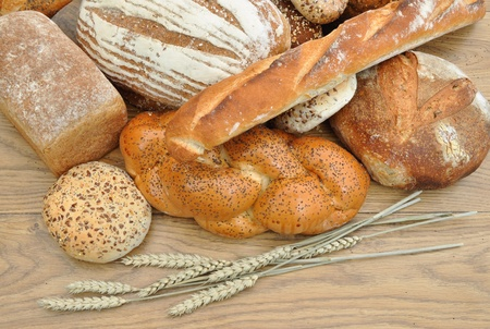 Assortment of bread loaves and baguettes with wheat spikes photo