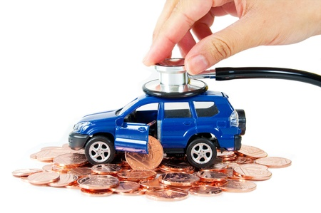 car insurance: Toy car with a stethoscope on top of stacks of coins