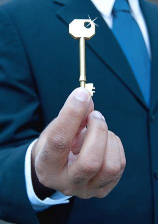 Businessman with shiny gold key  photo