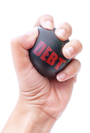 repossession: Hand squeezing a stress ball labeled with debt  Stock Photo