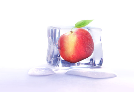 Fresh whole peach fruit frozen inside ice cube photo