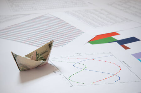 Dollar paper boat on financial data  photo
